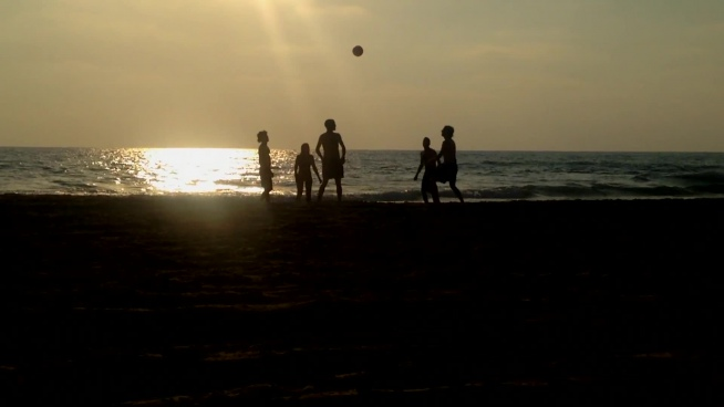 youth excited with football on beach at dusk