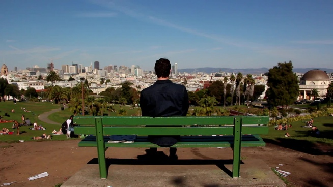 lonely man sitting on bench watching cityscape