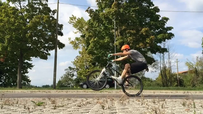 dynamic youth with bicycle performance on road