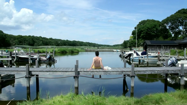 man relaxing on wooden bridge on calm river