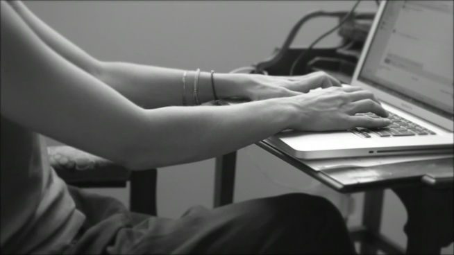 black white clip of woman typing on laptop