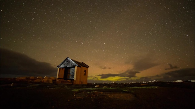clouds and stars motion above cottage at night