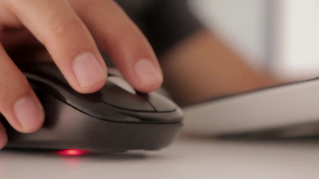 closeup of hands moving computer mouse