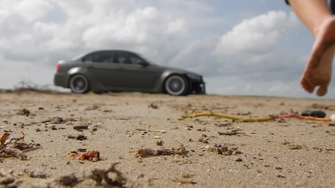 bokeh clip of man driving car on sand