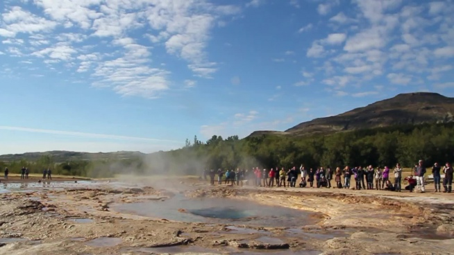 crowd watching natural water eruption on ground