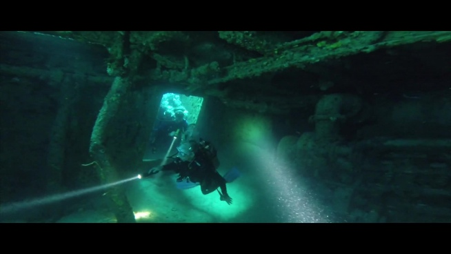 divers discovering wrecked ship in deep sea
