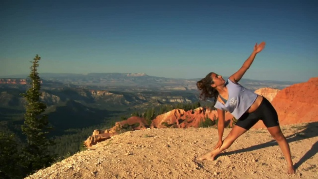 woman performing yoga exercise on high mountain
