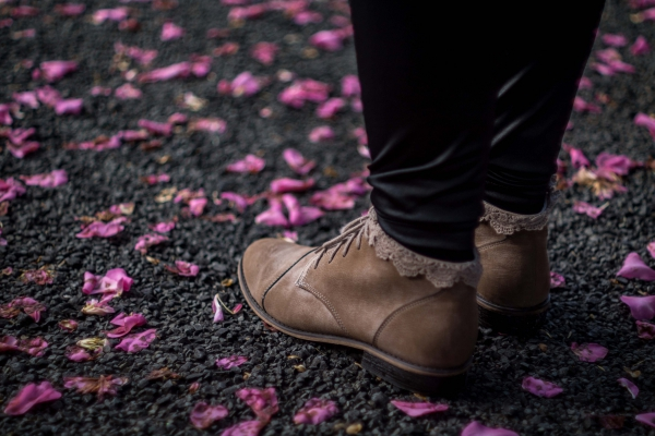 rumpled flowers surrounding feet with boots