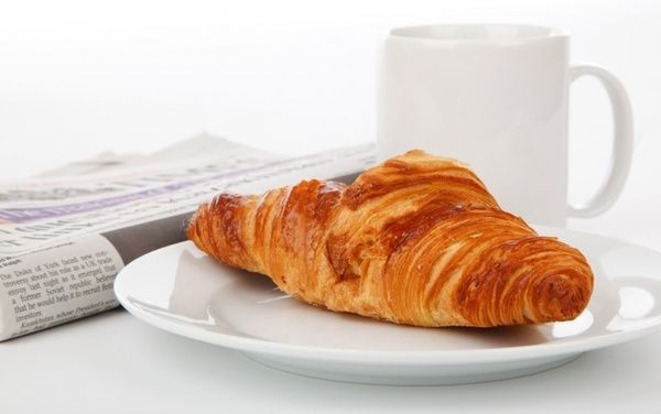 croissant newspaper and tea