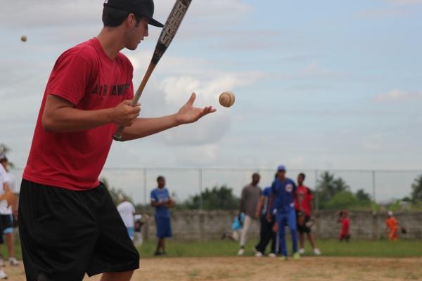 man hitting baseballs for practice drills