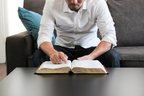 man on couch reading bible