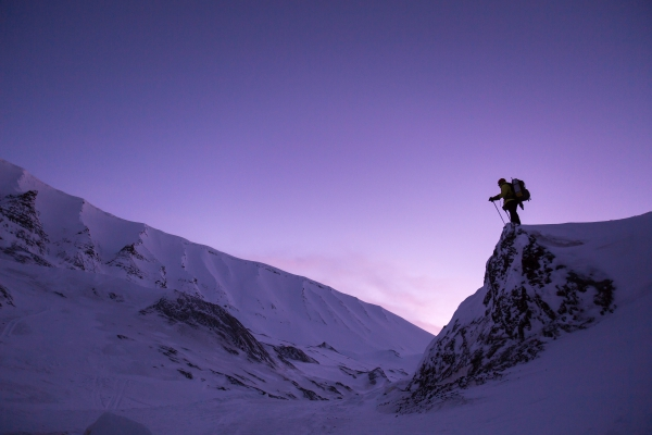 mountaineer standing on top of a rock