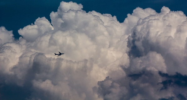 airplane flying in big white cloud
