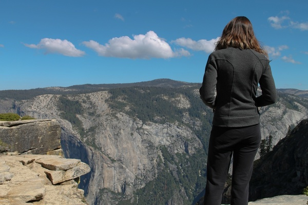woman on cliffs gazing at mountains