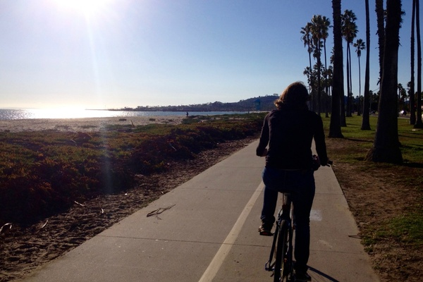 woman riding bicycle on path by beach
