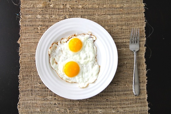 2 sunny side up eggs on plate with fork