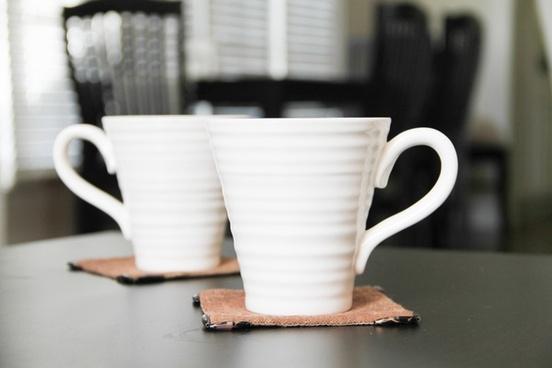 2 white coffee mugs on coasters