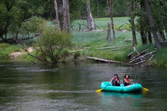 2 women paddling in a raft down a river