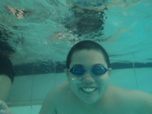 a boy smiling under water