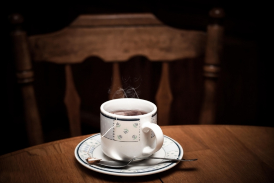 a cup of tea with metal spoon on the wooded table