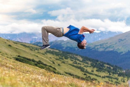 excited man performing acrobatics on hill