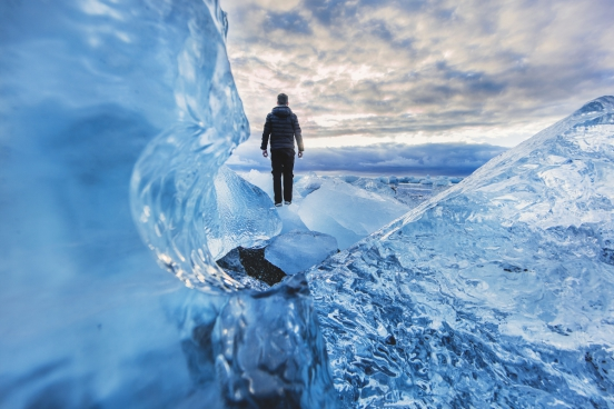 lonely man standing on frozen sea