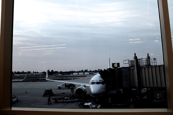 airplane docked at airport terminal through glass window