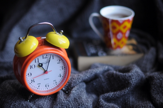 closeup of alarm clock near coffee cup