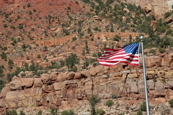 american flag waving in front of rocky cliffs