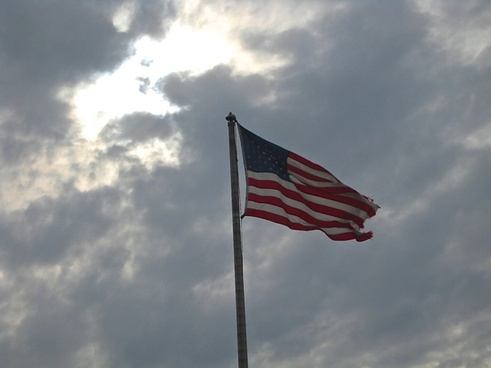american flag waving on cloudy sky