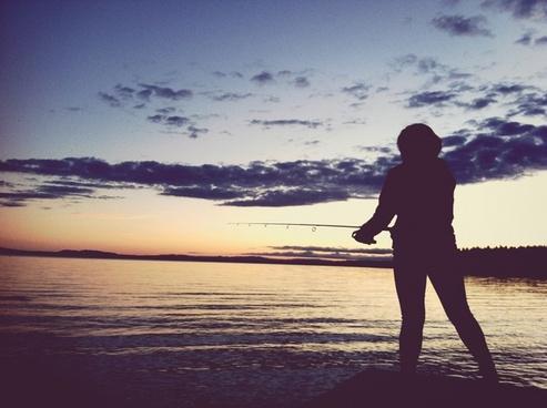 backlit beach coast dusk evening fisherman leisure