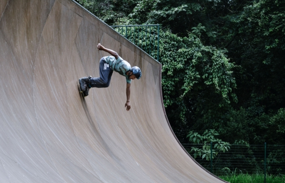 exciting man with roller skating on curved wall