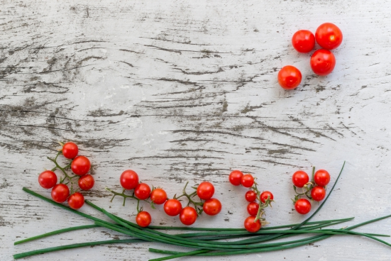 small red tomatoes on wooden background