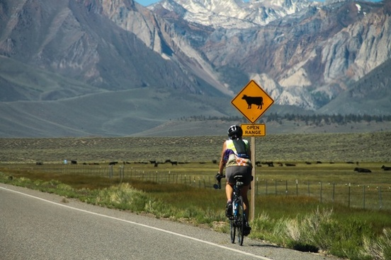 bicyclist on road in mountain countryside