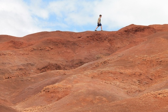 boy walking on red dirt hills