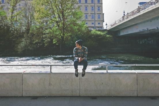 bridge building city concrete fence person river