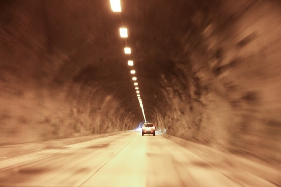 car drive down tunnel with overhead lights