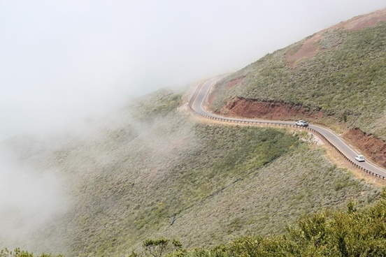 cars driving on winding mountain road in fog