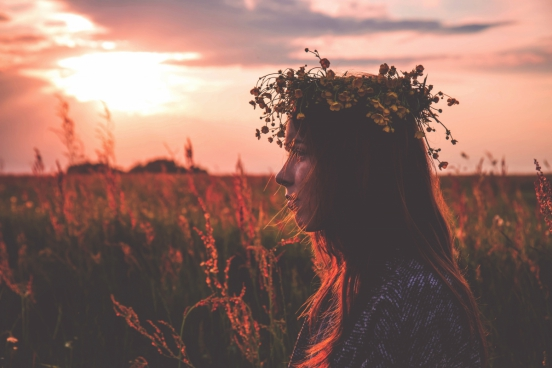 young girl with flowers wreath at sunset