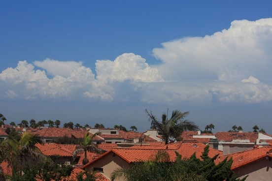 cloudscape over red tile roofs