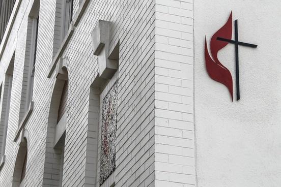 cross on white brick church building