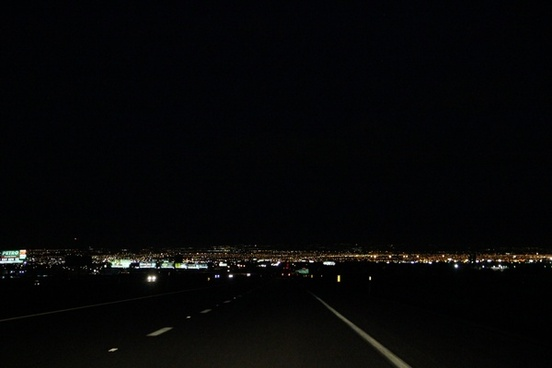 dark street leading to city lights at night