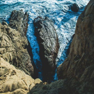 deep dark blue sea waves breaking on a rocks forming a sea