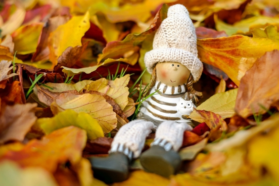 closeup of cute girl doll on yellow leaves