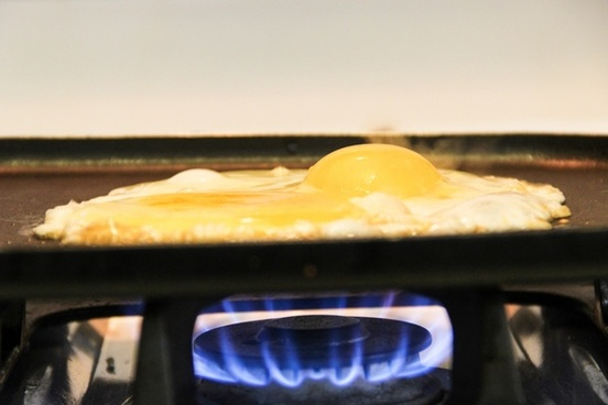 eggs cooking on frying pan over stove