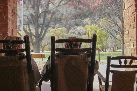 elderly couple sitting on wooden chairs