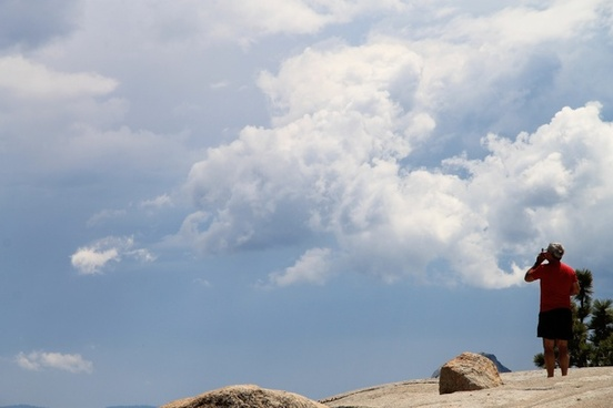 elderly man standing on rock under sky with puffy clouds