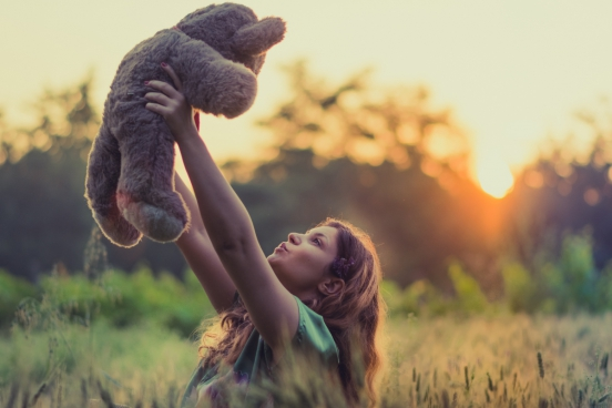 joyful woman with teddy bear under sunlight