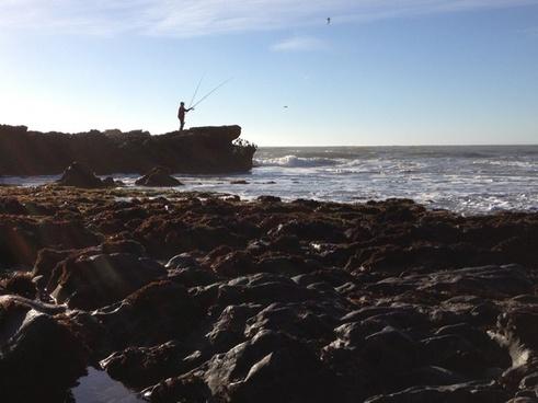 fisherman on rocky ocean shore