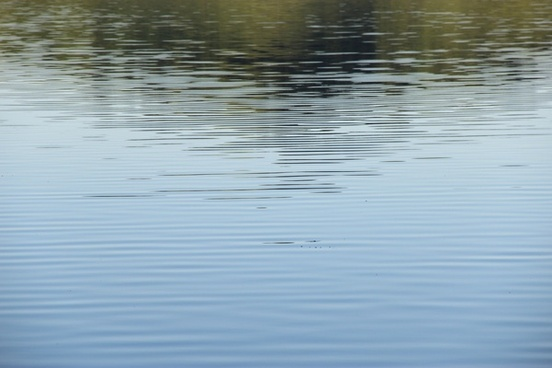 gentle water ripples with reflection of hill